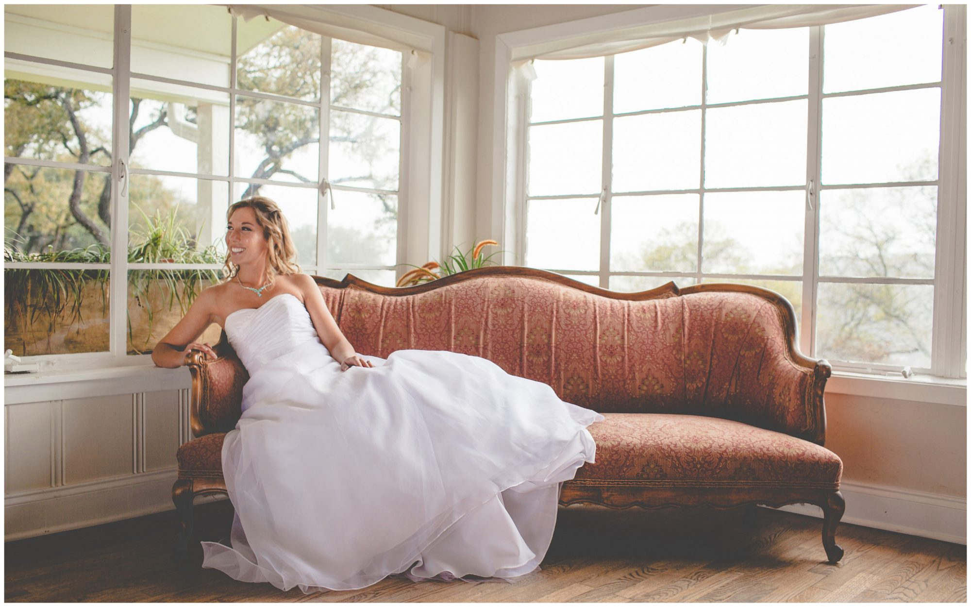 A bride lounges on an antique sofa at Hacienda Del Lago in Austin, Texas.