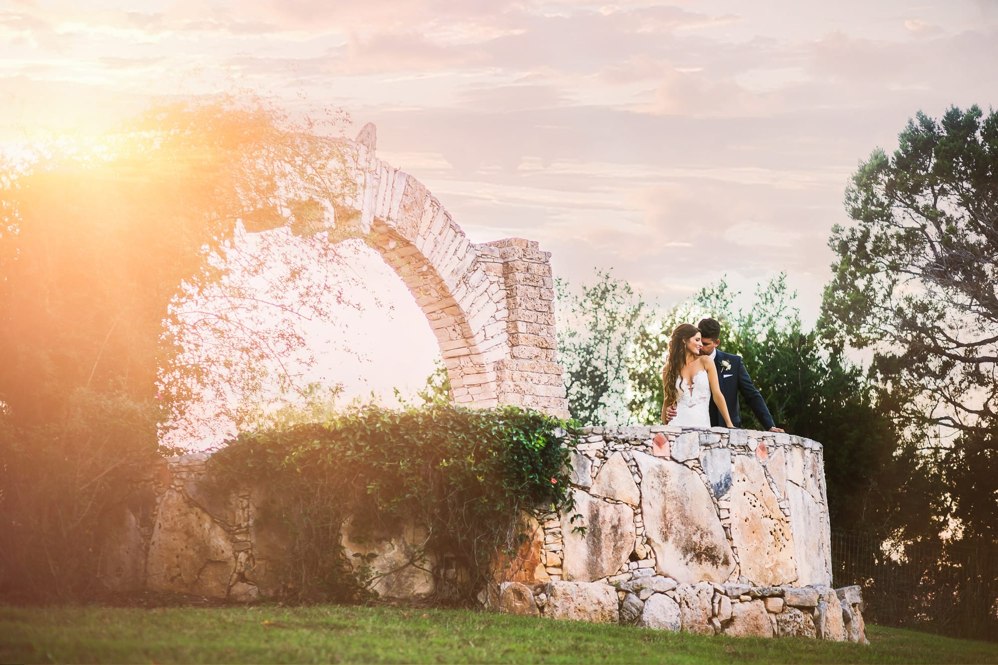 Bride and groom flirt while on edge of hill country view