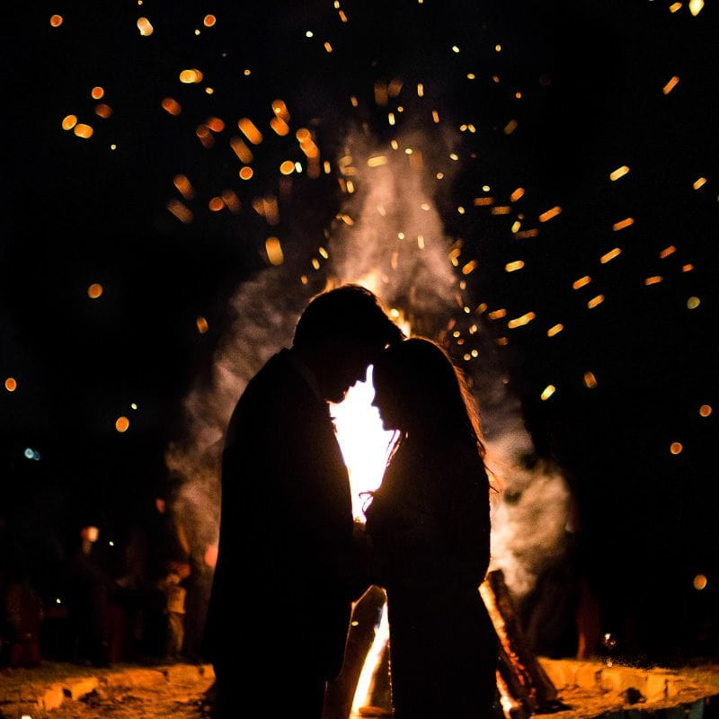A silhouette of a couple in front of a bonfire tapping their foreheads together