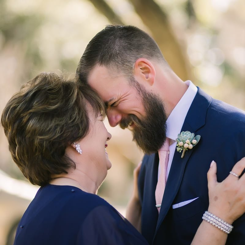 groom laughs with his mom as they embrace