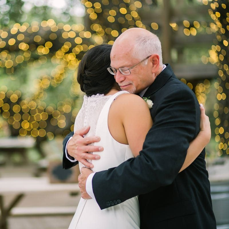 father of bride embraces his daughter at her wedding