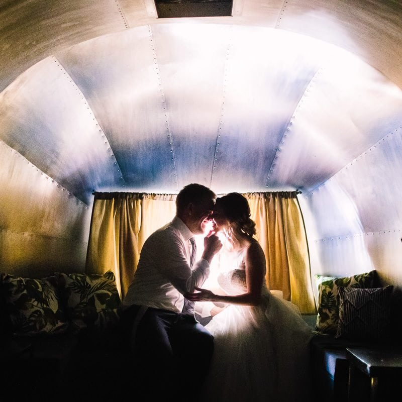 Bride and groom share a kiss at night inside of airstream trailer