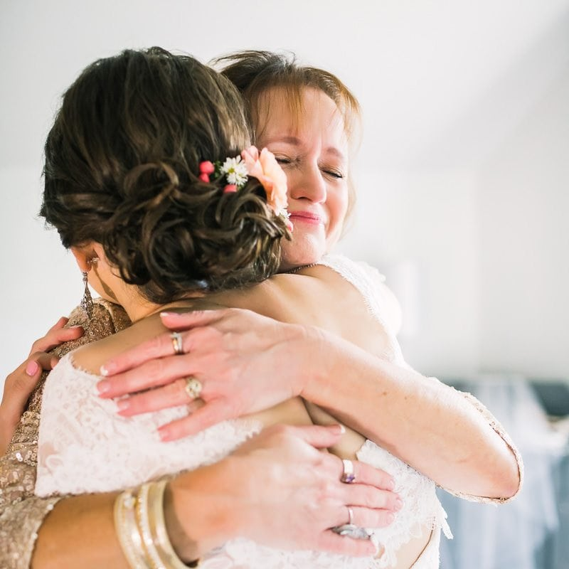 mother embraces her daughter before wedding ceremony