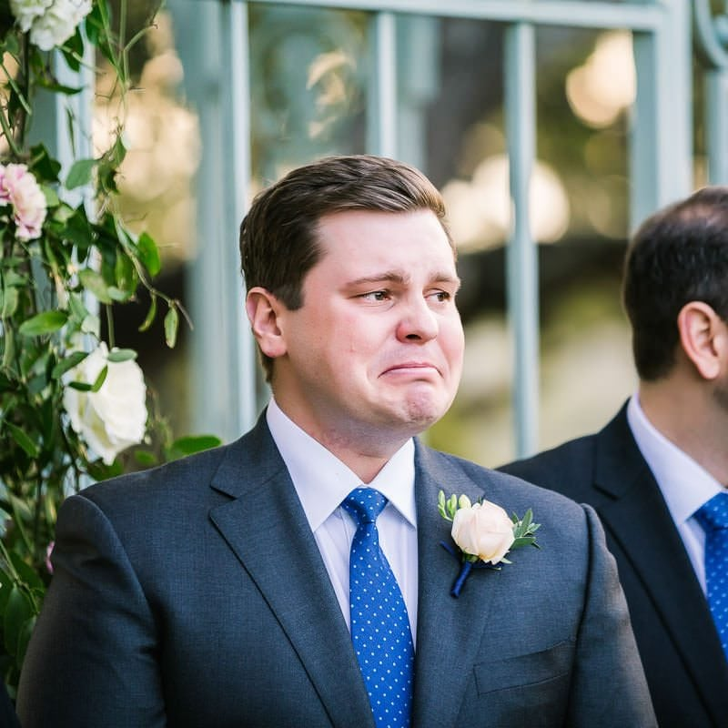 groom with tears in his eyes looks at his bride walking down the aisle