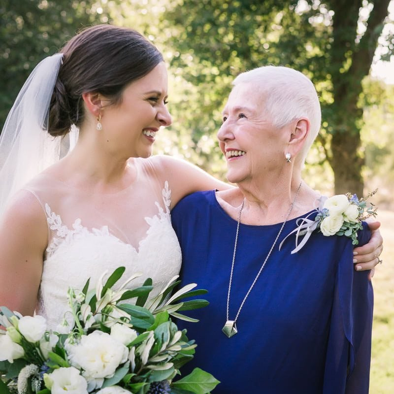 bride and her grandmother smile at each other