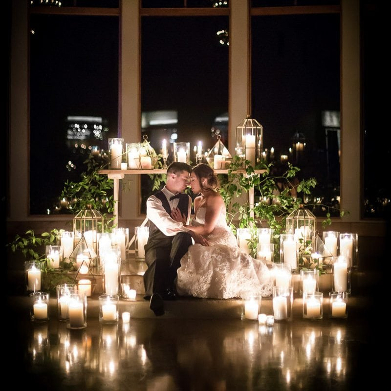 Bride and groom sit on steps of chapel at night and have romantic moment surrounded by candles