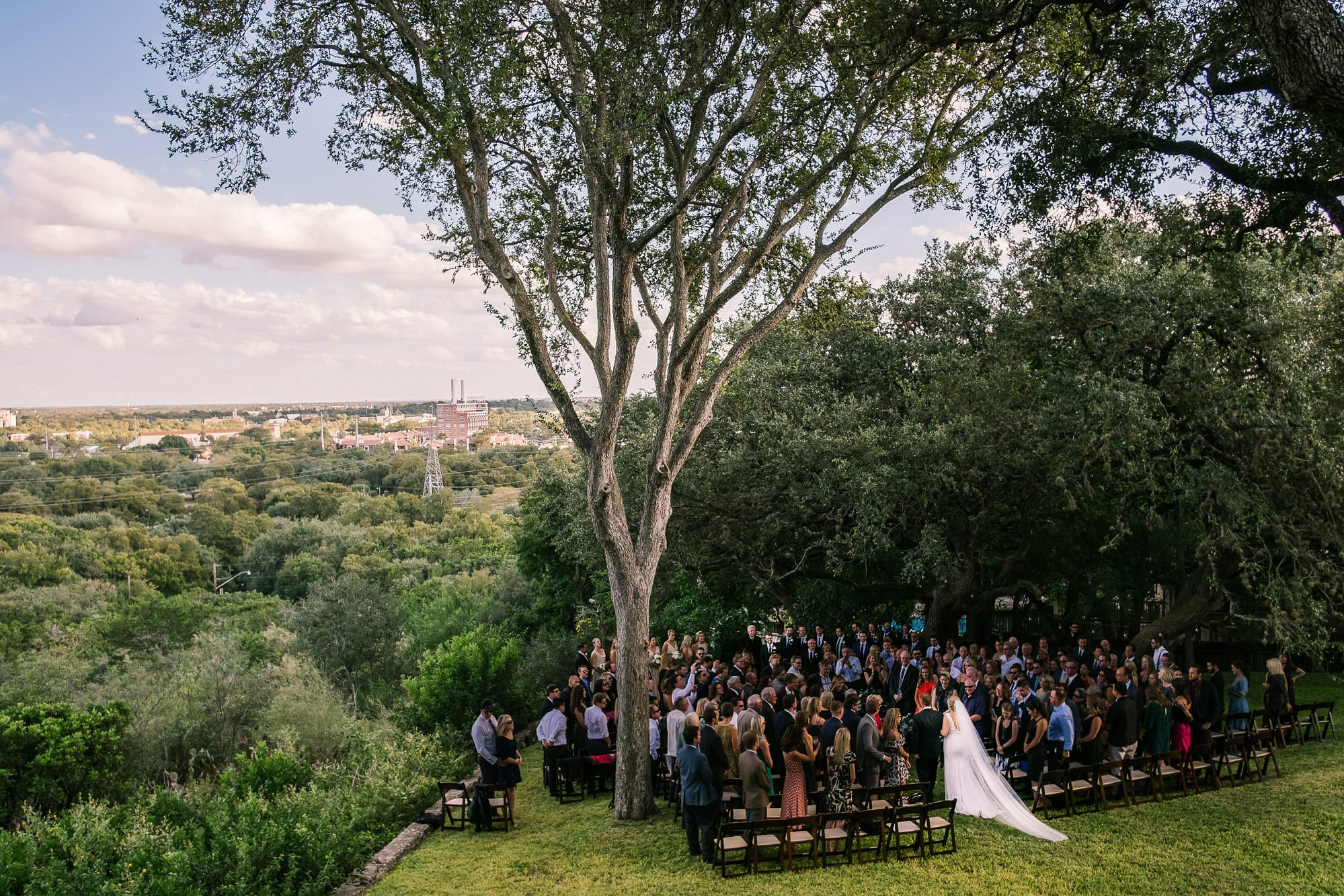 Father of the bride walks her down the aisle at ceremony on edge of sweeping vista