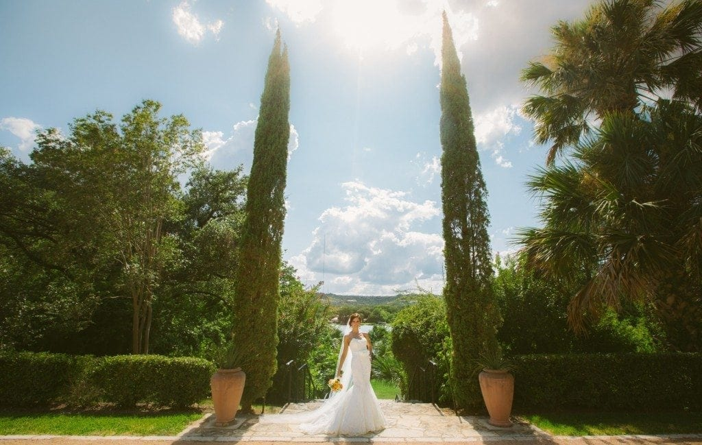 Bride stands in the garden at Laguna Gloria with a bright blue sky around her.