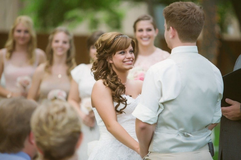 The bride looks at the groom while saying their vows during the wedding ceremony at Oak Tree Manor.