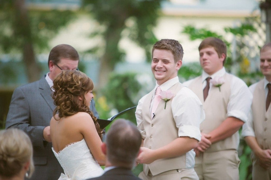 The groom smiles at the bride underneath the large oak tree during their Oak Tree Manor wedding ceremony.
