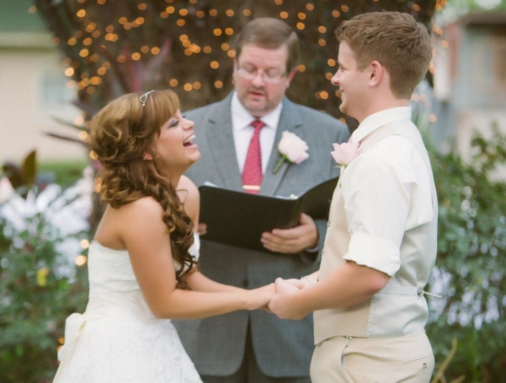 The bride and groom laugh together during their Oak Tree Manor wedding ceremony.