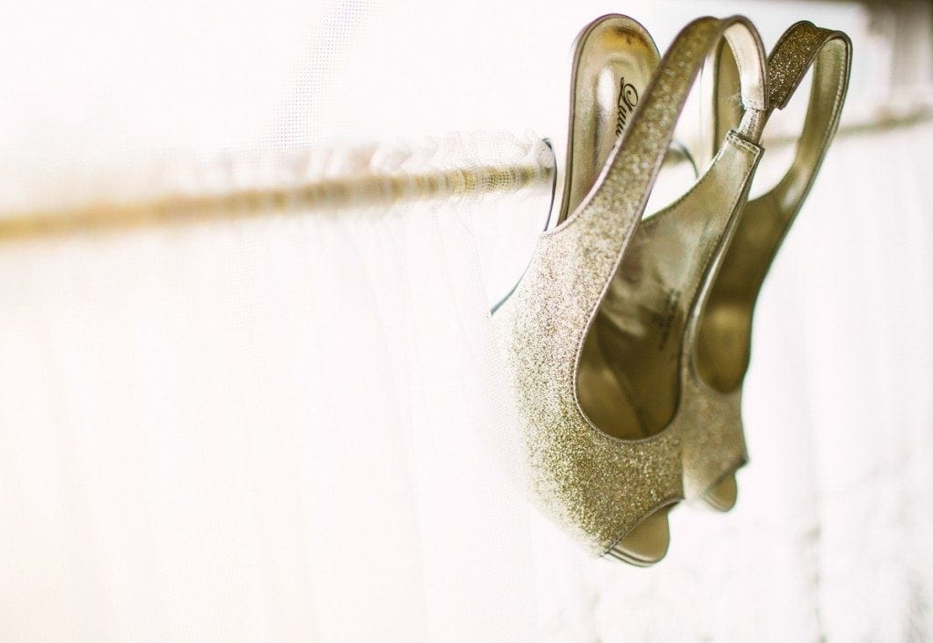 Bride's shoes hang from the window of a vintage airstream trailer at Three Points Ranch wedding venue in Dripping Springs, TX.