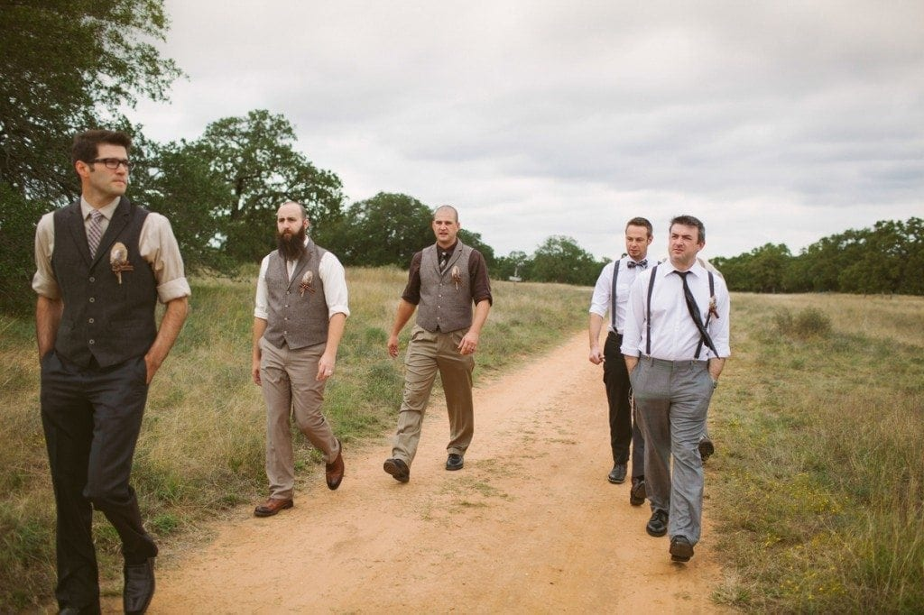 Groomsmen walk down the dirt road between fields at Three Points Ranch wedding venue.