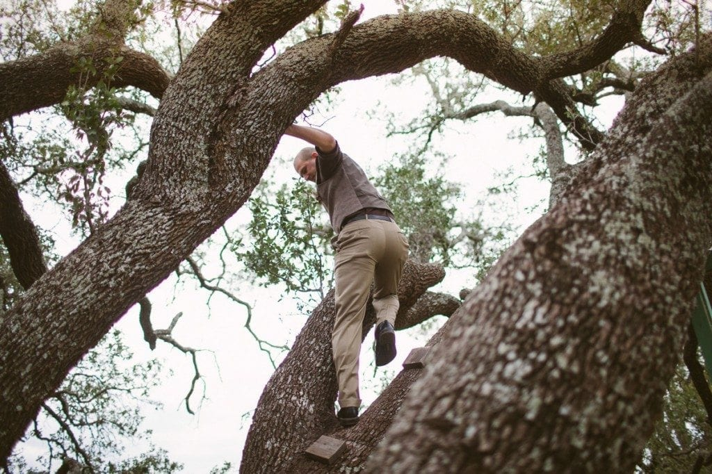 Groomsman climbs a tree at the ceremony site.