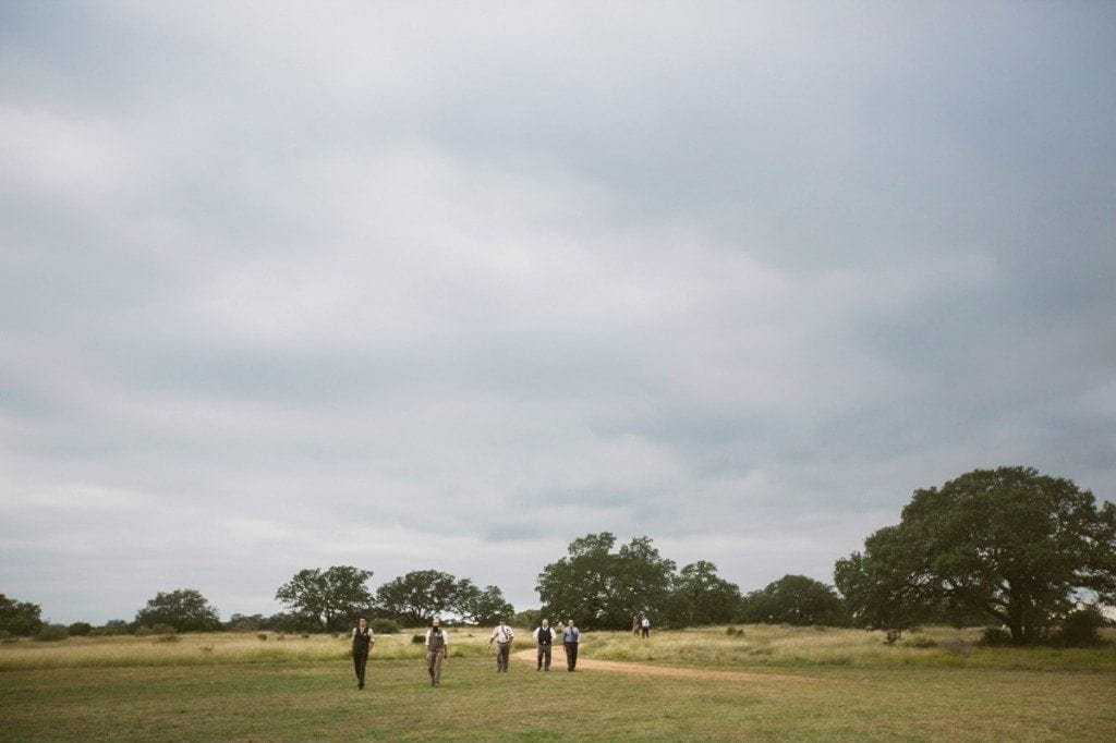 Groomsmen walk through an open field on the way to the wedding ceremony at Three Points Ranch.