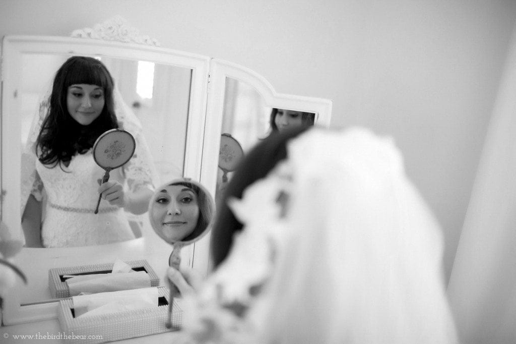 Bride looks in the mirror in Dove Cottage at the Heritage House in Dripping Springs, TX