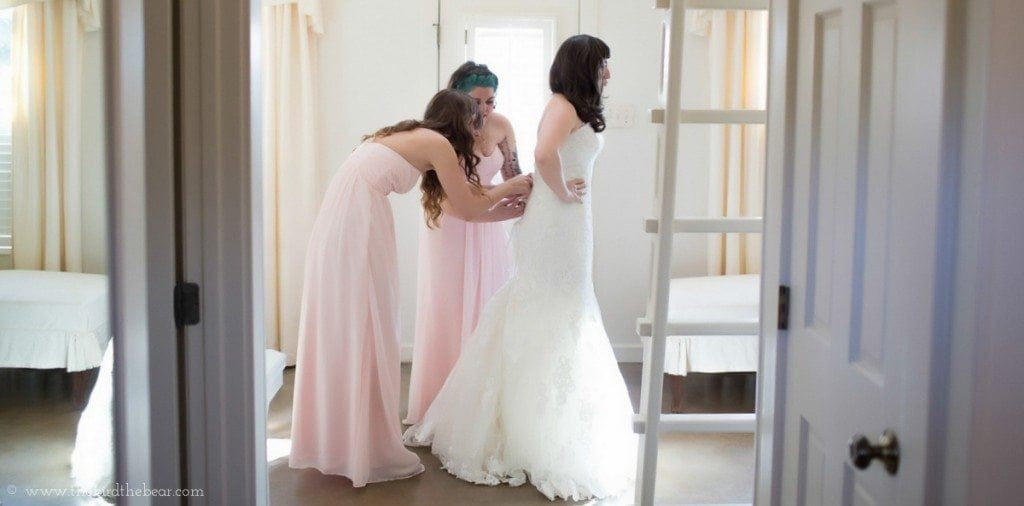 Bridesmaids tie the back of the bride's wedding gown while getting ready in the bridal suite.