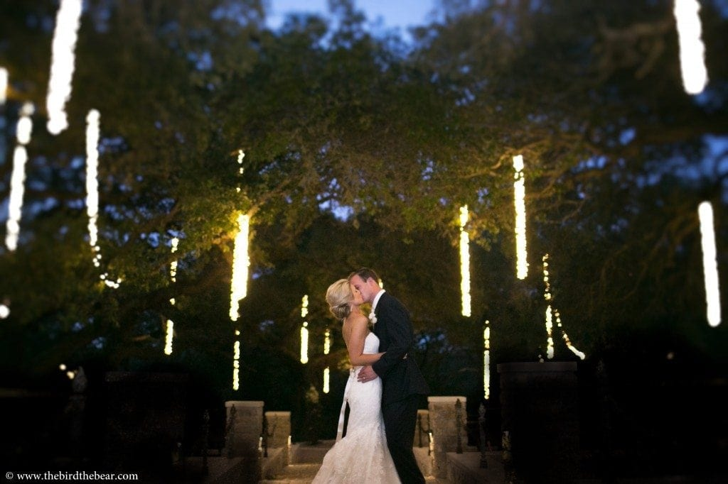 Bride and Groom kiss under the lights at Sacred Oaks at Camp Lucy in Dripping Springs, TX.