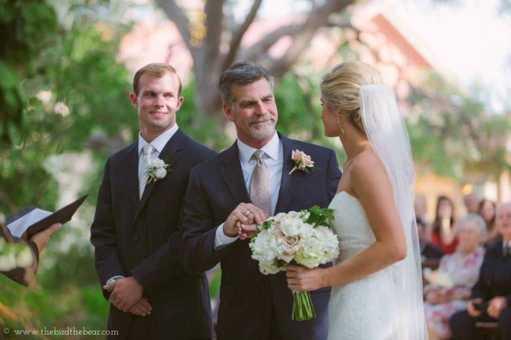 The bride's father hands her off to the groom at the front of the aisle at Sacred Oaks.