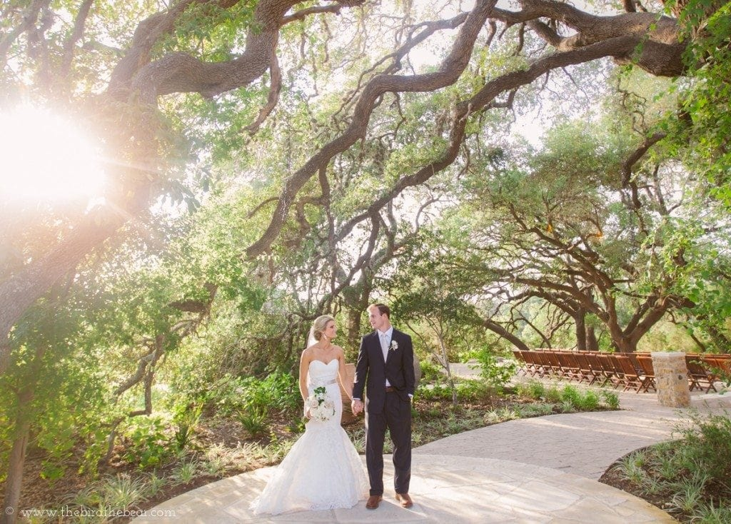 Bride and groom stand in the sunshine at Sacred Oaks Camp Lucy in Dripping Springs, TX.