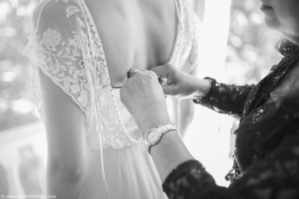 mother of the bride tying bride's gown