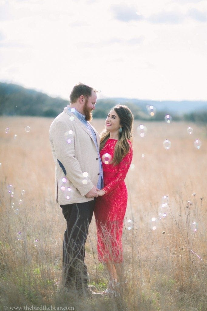 Creative engagement photos with bubbles and a hot pink dress in Austin, TX