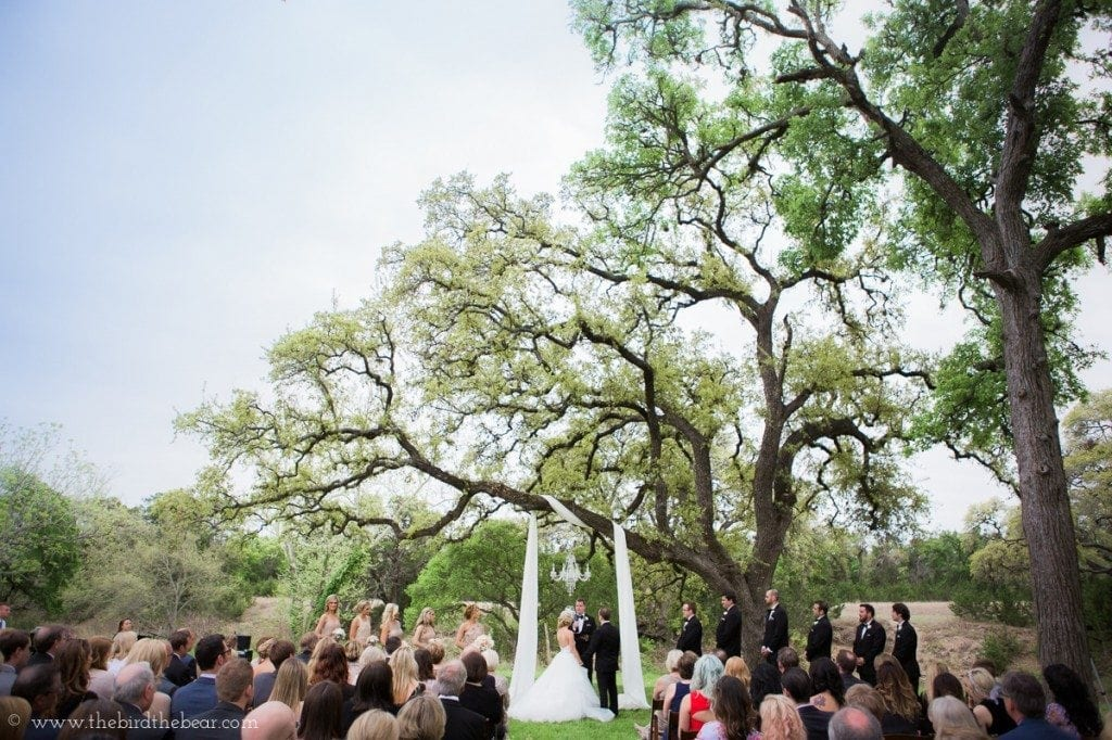 Pecan springs ranch wedding ceremony under the trees in austin, tx