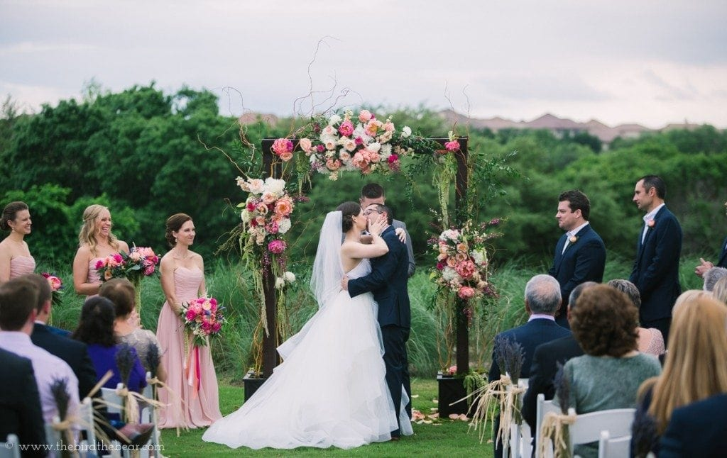 Bride and groom share their first kiss as man and wife at the University of Texas Golf Club in Austin.