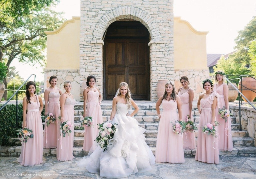 Bridesmaids in blush pink bridesmaids dresses with bride in vera wang bridal gown.