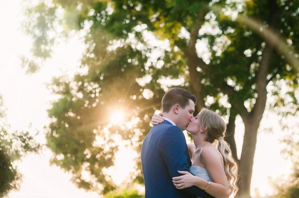 Bride and groom kiss at sunset at Barr Mansion in Austin, TX