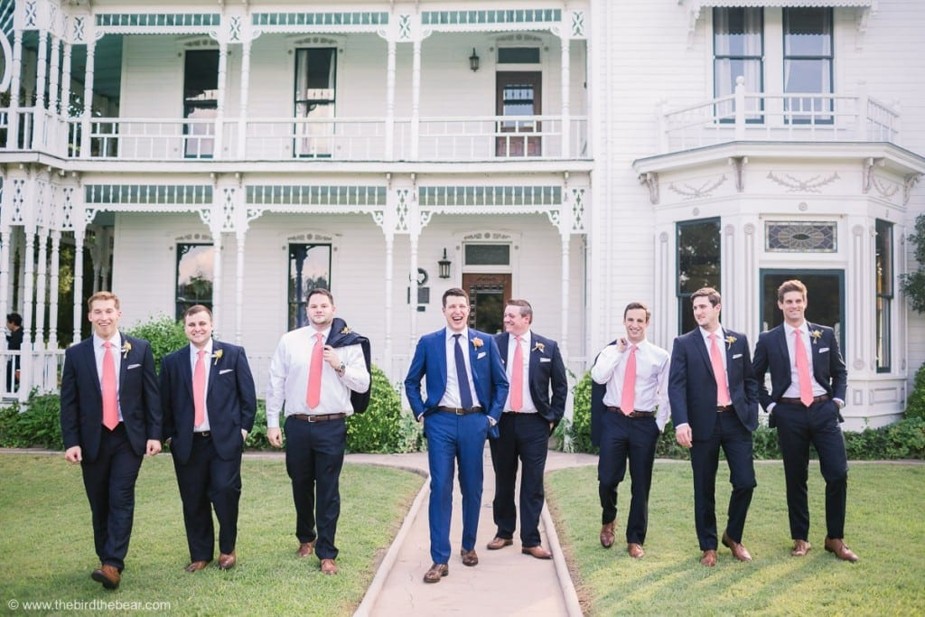 Groom and Groomsmen laugh as they walk outside of beautiful house
