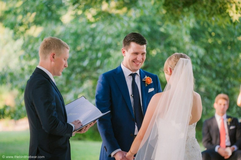 Groom holds hands with bride for the first time at wedding ceremony