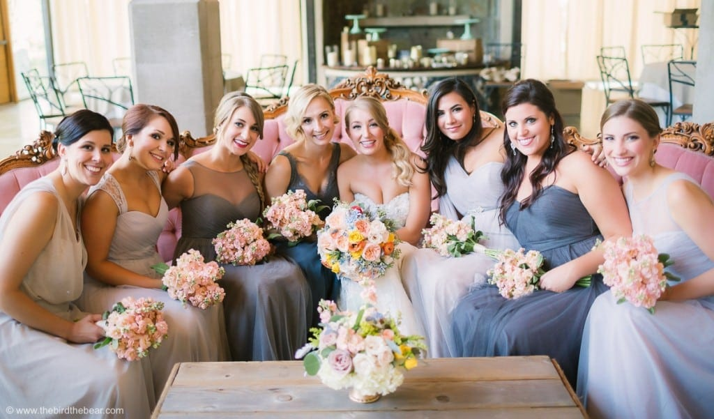 group photo of bridesmaids with bride on pink couch