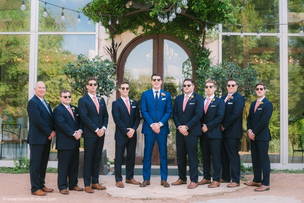 Groomsmen take sunglasses shot in front of reception hall