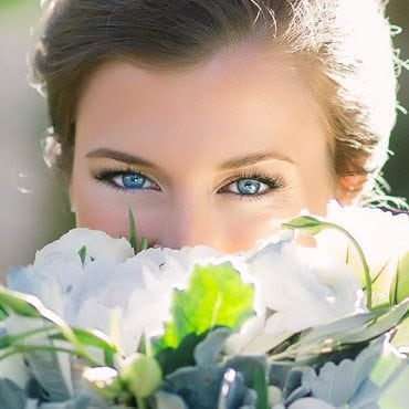 Bride looks over her bouquet of flowers and smiles with her eyes
