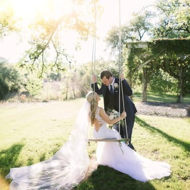 Bride sitting on swing looks at groom while her veil flows