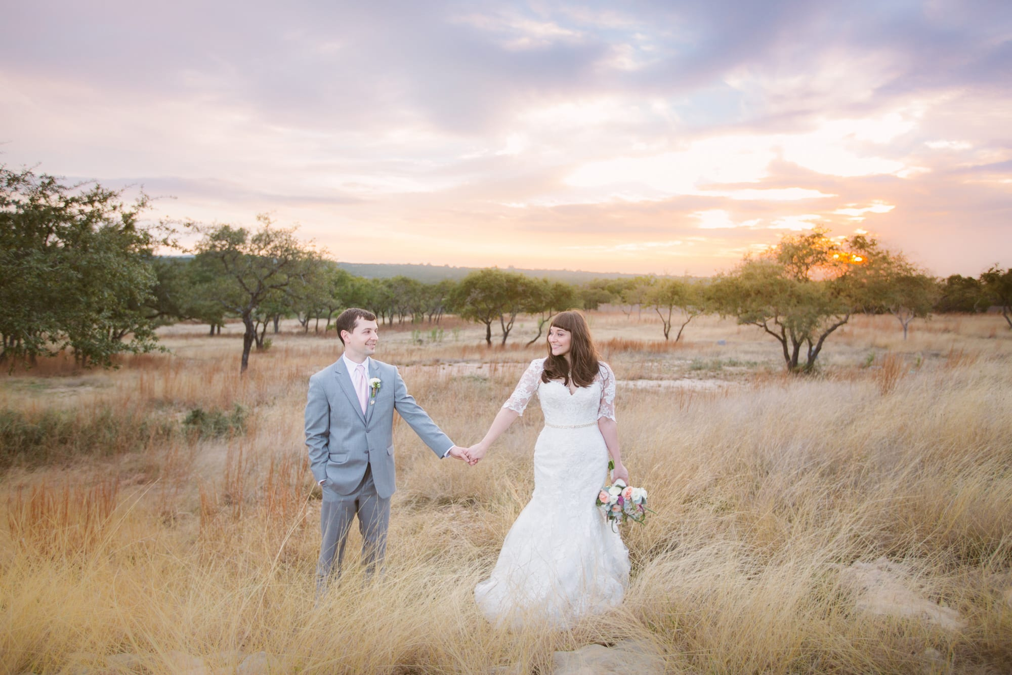 A bride and groom stand in field holding hands while photographers capture the romance